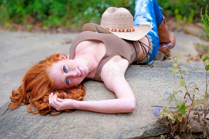 可爱的蓝色女牛仔被注视的头发红色 免版税图库摄影