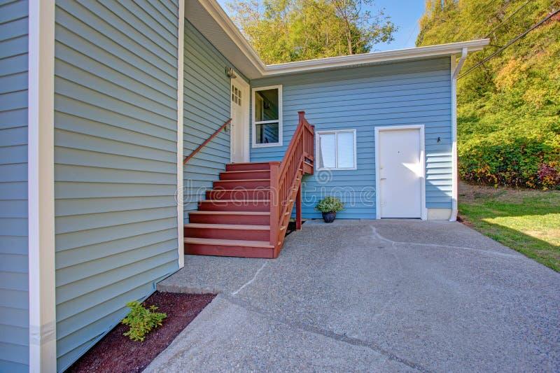 可爱的蓝色家庭外部以红色楼梯为特色 免版税库存图片