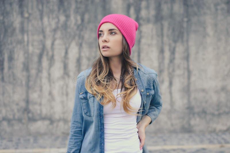 可爱的行家女孩在白色T恤杉、摆在对灰色墙壁的牛仔裤衬衣和桃红色帽子穿戴了 街道照片射击 牛仔布 库存照片