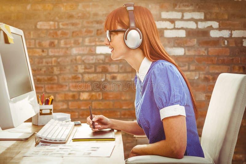 可爱的行家妇女的综合图象有耳机的使用图形输入板 免版税库存图片
