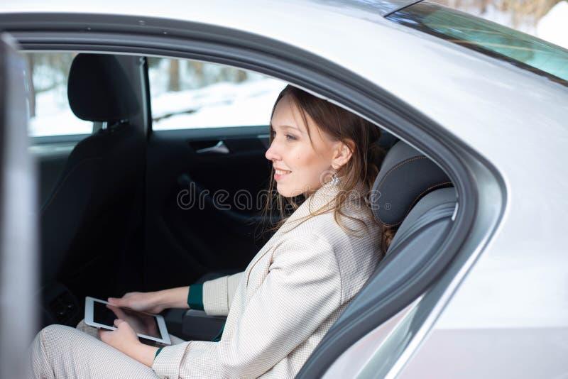 可爱的行政女性经理与在汽车的后座的一种片剂一起使用 图库摄影