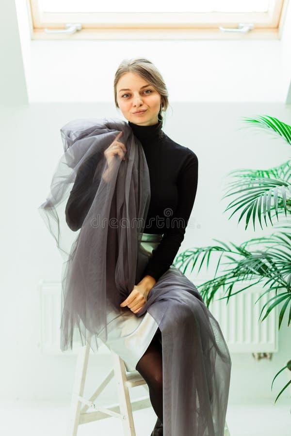 可爱的裁缝,坐椅子和拿着织品 免版税库存图片