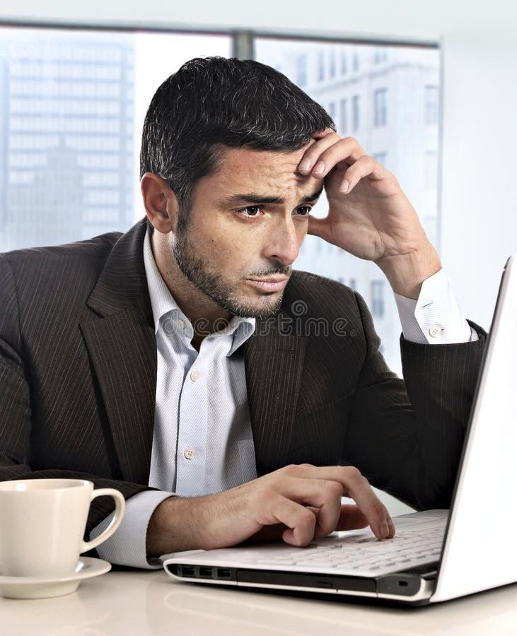 可爱的西班牙商人与看起来的计算机一起使用被注重的和担心的饰面工作问题 免版税图库摄影