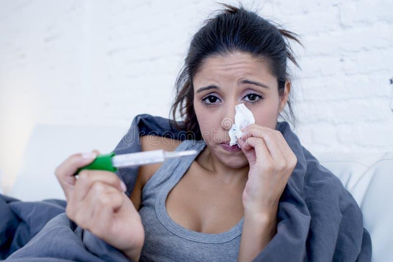 年轻可爱的西班牙在寒冷和流感的妇女说谎的病残在家长沙发在牢骚疾病症状 免版税库存图片