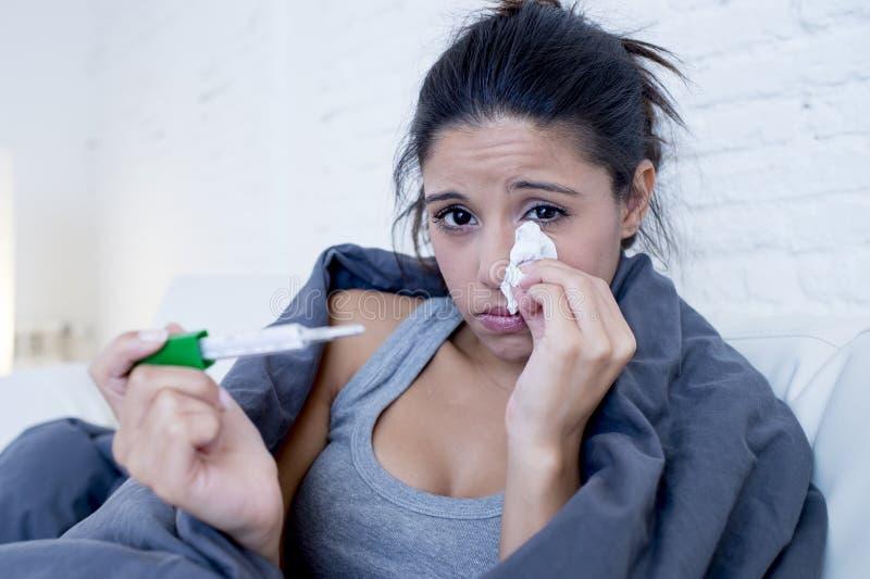 年轻可爱的西班牙在寒冷和流感的妇女说谎的病残在家长沙发在牢骚疾病症状 图库摄影