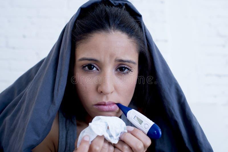 年轻可爱的西班牙在寒冷和流感的妇女说谎的病残在家长沙发在牢骚疾病症状 免版税图库摄影