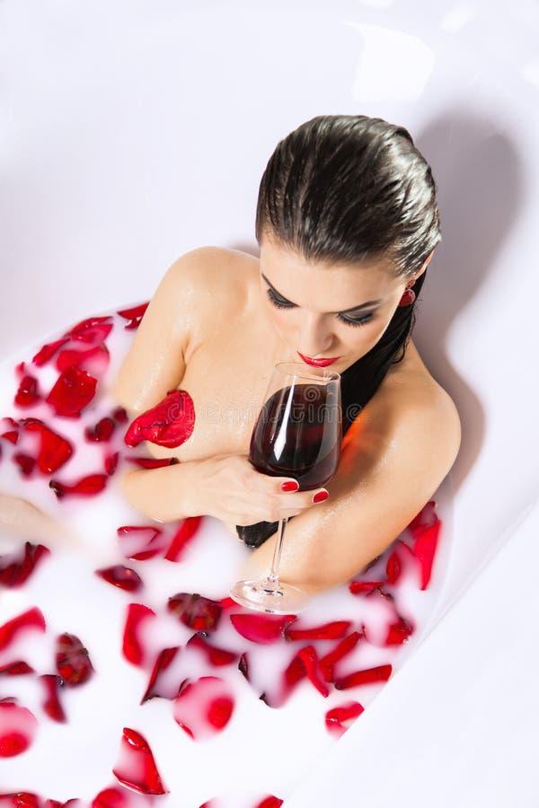 可爱的赤裸女孩享用一杯在浴的酒用牛奶 免版税库存图片