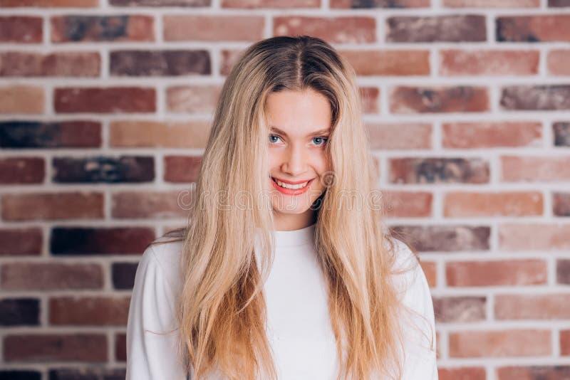 可爱的迷人的年轻白肤金发的妇女画象有长发的在红砖背景 逗人喜爱的男女共学女孩微笑和看看 免版税库存照片