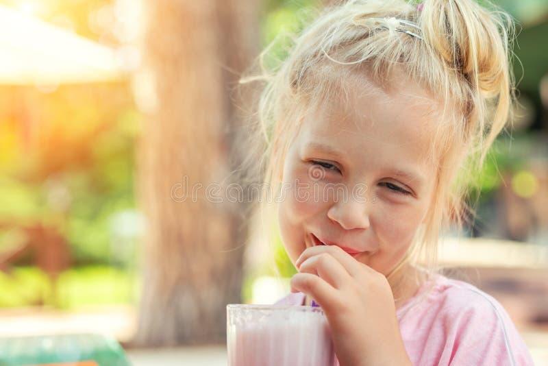 可爱的逗人喜爱的啜饮新鲜美草莓奶昔coctail的学龄前儿童白种人白肤金发的女孩画象在咖啡馆户外 免版税库存照片
