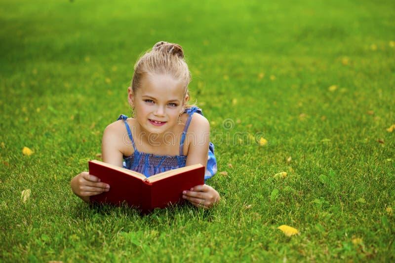 可爱的逗人喜爱的小女孩阅读书外面在草 库存照片
