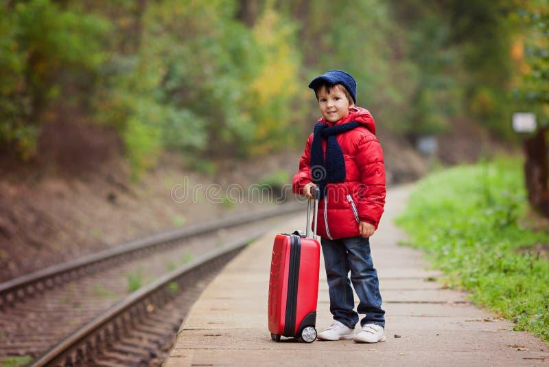 可爱的逗人喜爱的小孩,男孩,等待在一个火车站fo 库存照片
