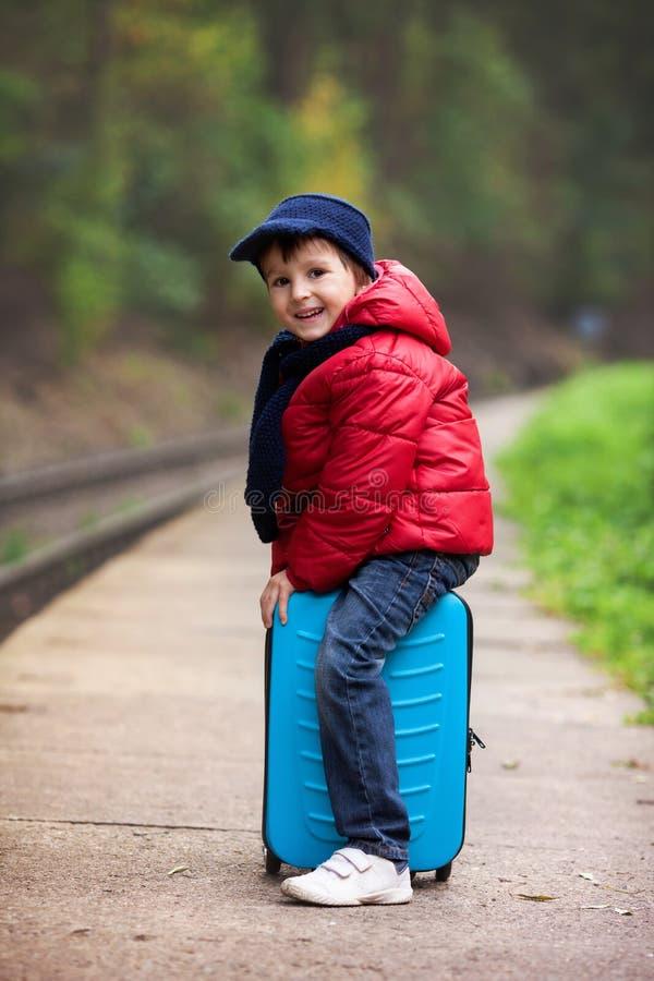 可爱的逗人喜爱的小孩,男孩,等待在一个火车站fo 免版税库存图片