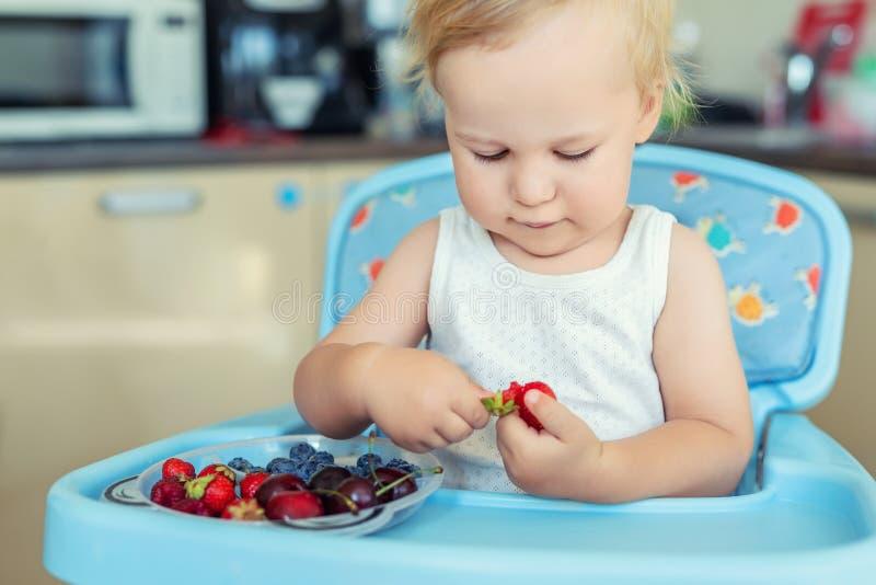 可爱的逗人喜爱的白种人白肤金发的小孩男孩喜欢品尝在家坐在高脚椅子的不同的季节性新鲜的成熟有机莓果 免版税库存照片