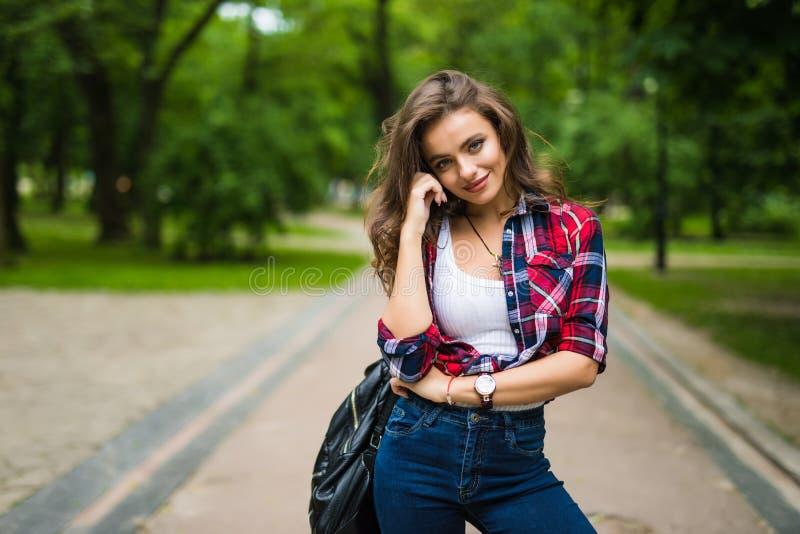 可爱的都市女孩画象有背包的在街道愉快的微笑的妇女 免版税库存图片