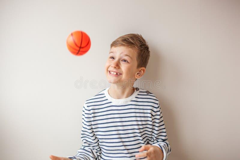 可爱的金发男孩投掷的篮球在天空中 库存照片