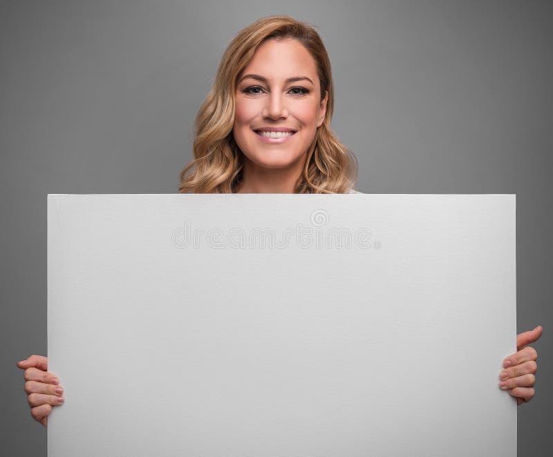 可爱的金发碧眼的女人拿着您的文本或图象的白色空白的空的海报在灰色背景 免版税库存照片