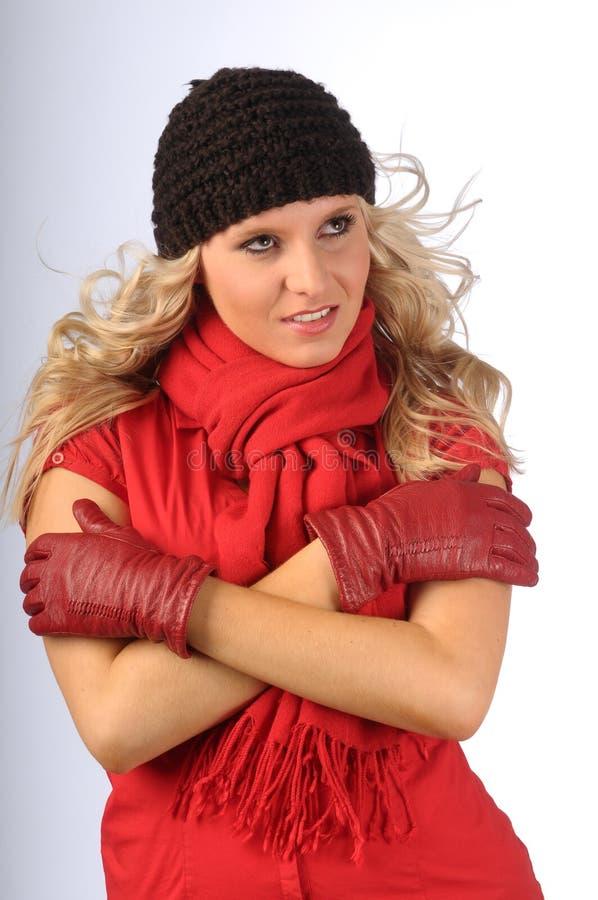 可爱的金发碧眼的女人给冬天穿衣 免版税库存照片