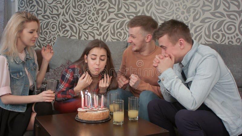 可爱的青少年的女孩在家庆祝她的与朋友的生日并且吹灭在蛋糕的蜡烛并且喝桔子 库存照片