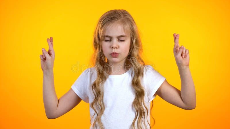 可爱的青春期前的梦想生日礼物信仰的女孩横渡的手指在运气 免版税库存图片