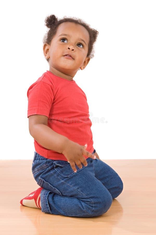 可爱的非洲婴孩跪下来 免版税库存图片