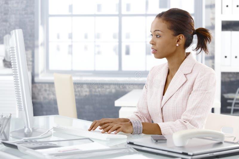 可爱的非洲的女实业家在工作 免版税库存图片