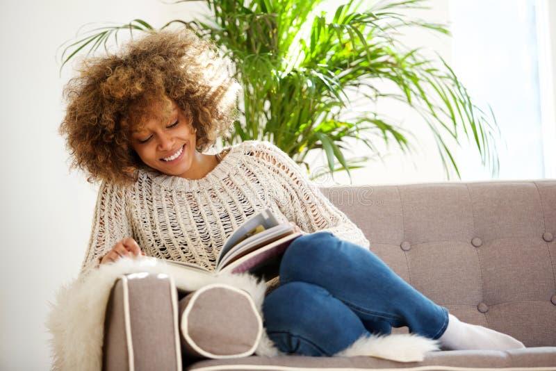 可爱的非裔美国人的妇女坐沙发阅读书 免版税图库摄影