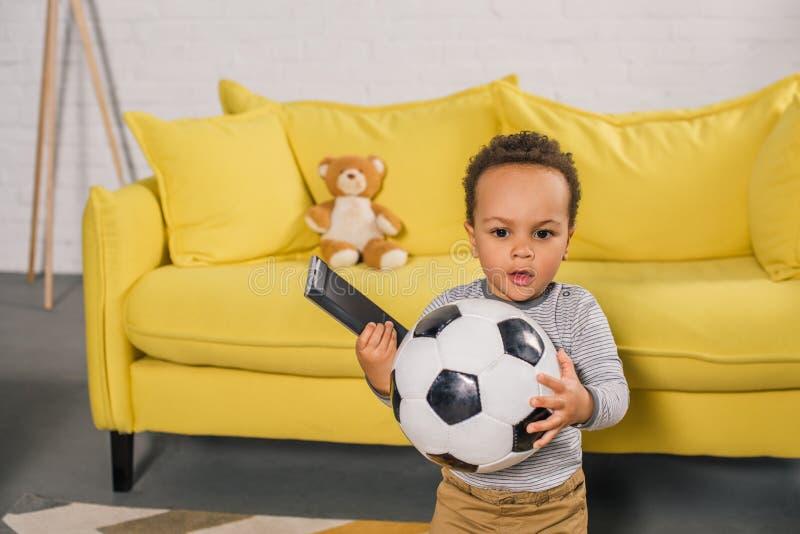 可爱的非裔美国人的小孩拿着足球的和遥远的控制器 库存图片