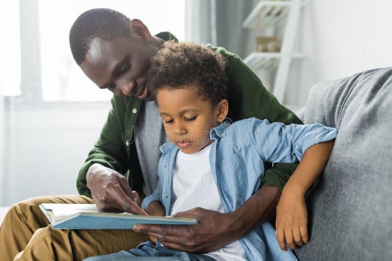 可爱的非裔美国人的父亲和儿子读书 免版税库存照片