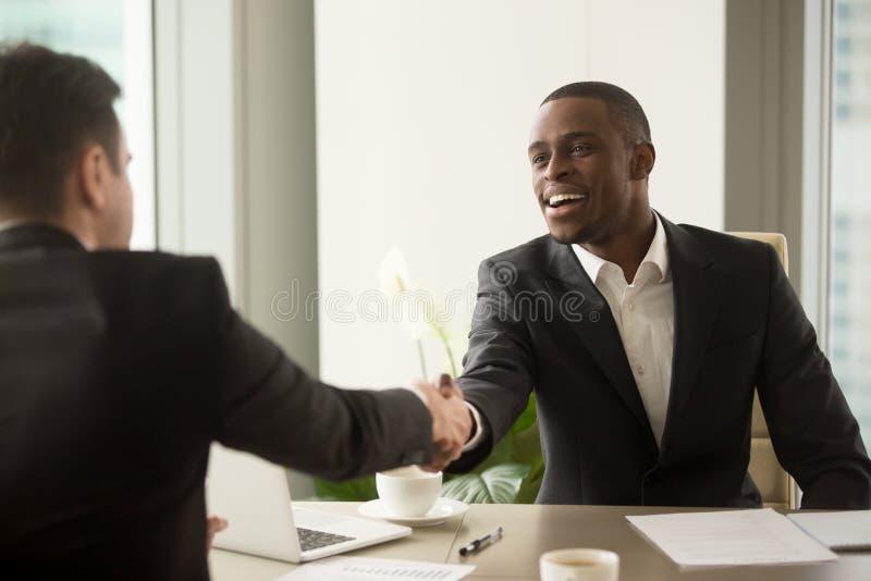 可爱的非洲商人和白种人商务伙伴ha 免版税库存图片