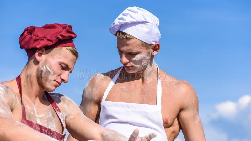 可爱的面包师队与面粉一起使用,准备面团 帽子和围裙的面包师,揉面团 库存照片