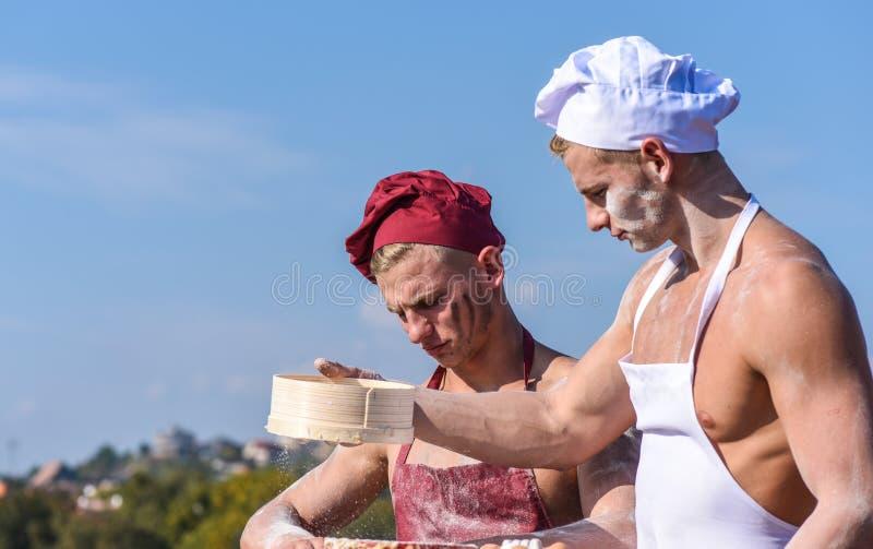 可爱的面包师队与面粉一起使用,准备面团 帽子的面包师和围裙与筛子,揉的面团一起使用 库存图片
