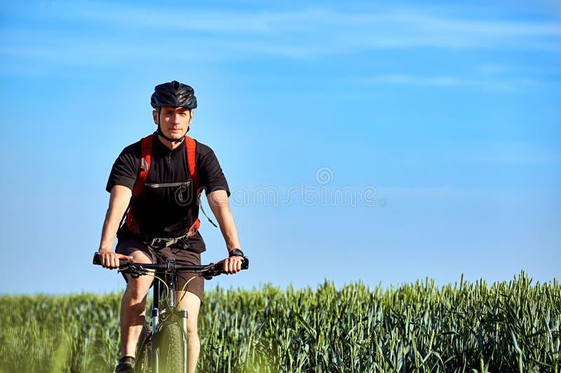 可爱的骑自行车者在一个领域的路乘坐在一个明亮的晴天反对蓝天 库存照片