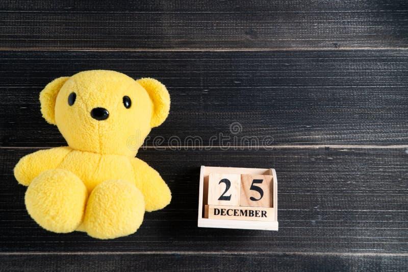 可爱的黄色玩偶和木在圣诞节日期设置的块日历12月25日在黑木背景的 概念的25/12我 库存照片