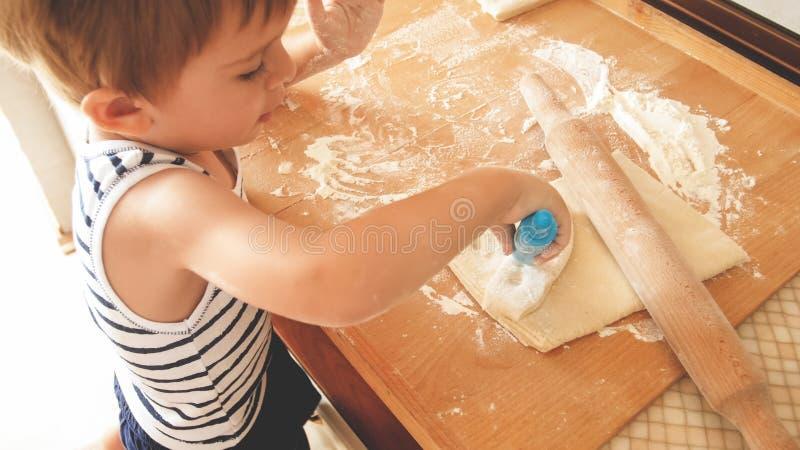可爱的3与木rooling的别针的岁小孩男孩烘烤的曲奇饼和滚动面团特写镜头画象  ?? 库存图片