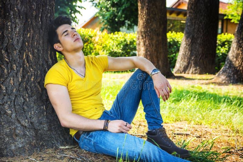 可爱的年轻人在休息反对树的公园 库存照片