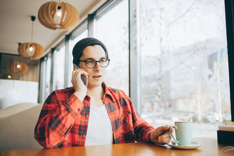 可爱的年轻人或自由职业者在咖啡馆和饮用的茶坐 库存照片
