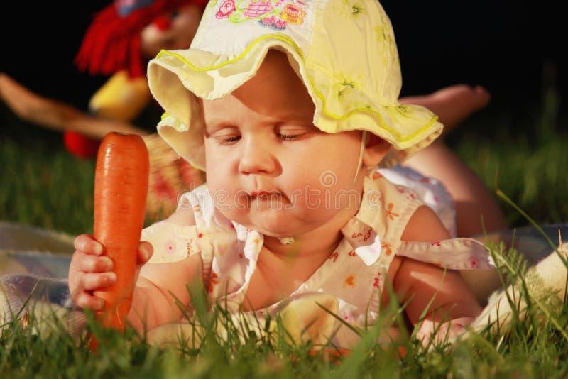 可爱的婴孩在他的手上的拿着一棵红萝卜 库存图片
