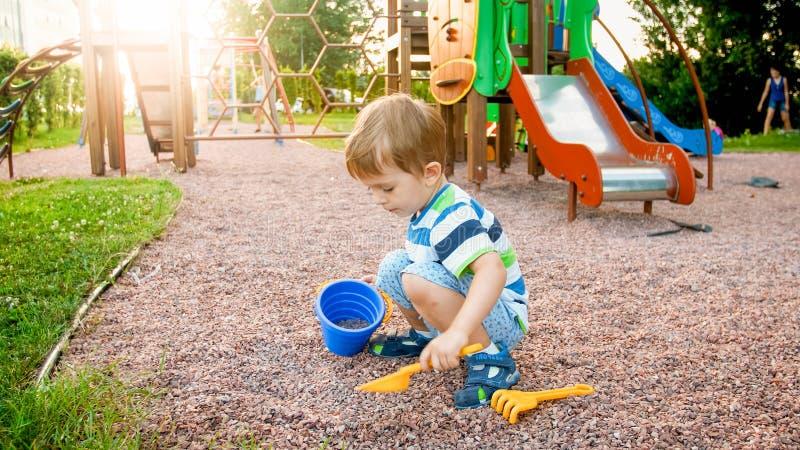 可爱的3岁照片小男孩坐操场和开掘的沙子与小塑料铁锹和桶 免版税库存照片