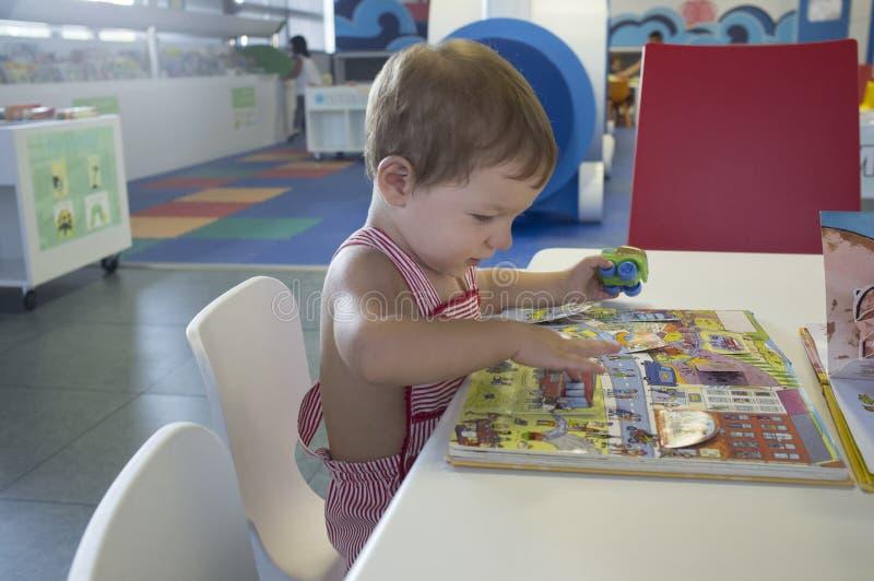 可爱的2年男孩在图书馆的浏览故事 免版税库存照片