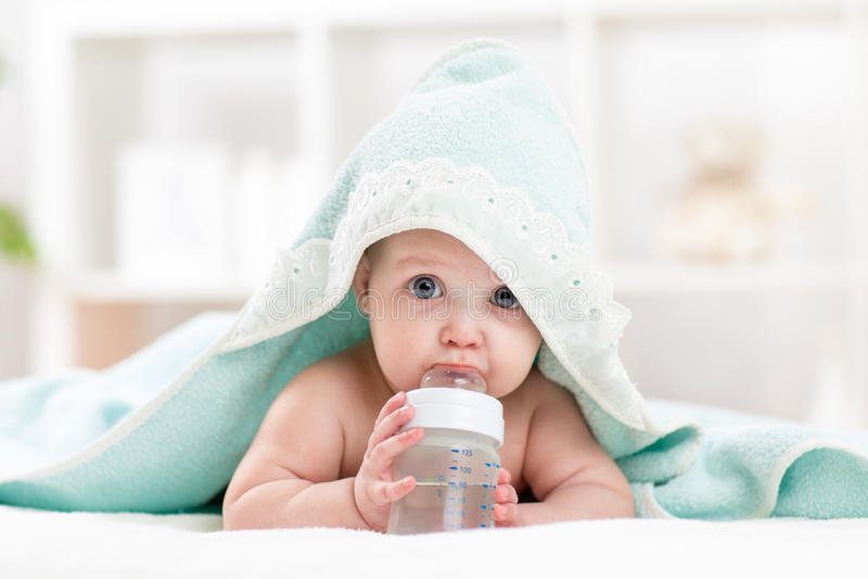 可爱的从瓶的儿童婴孩饮用水 免版税图库摄影