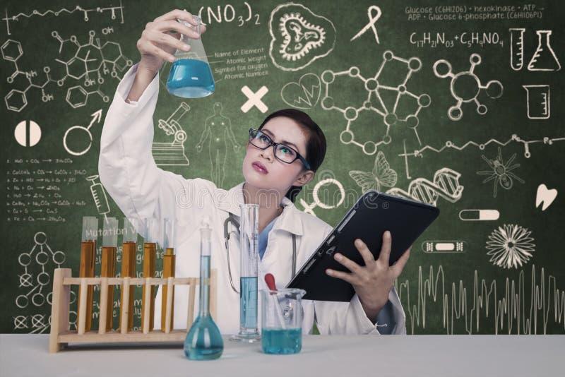 可爱的医生在实验室审查化学制品 免版税库存照片