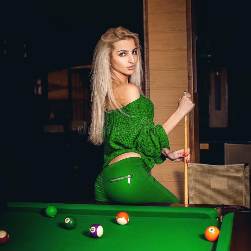 可爱的年轻白肤金发的夫人演奏台球 免版税库存图片