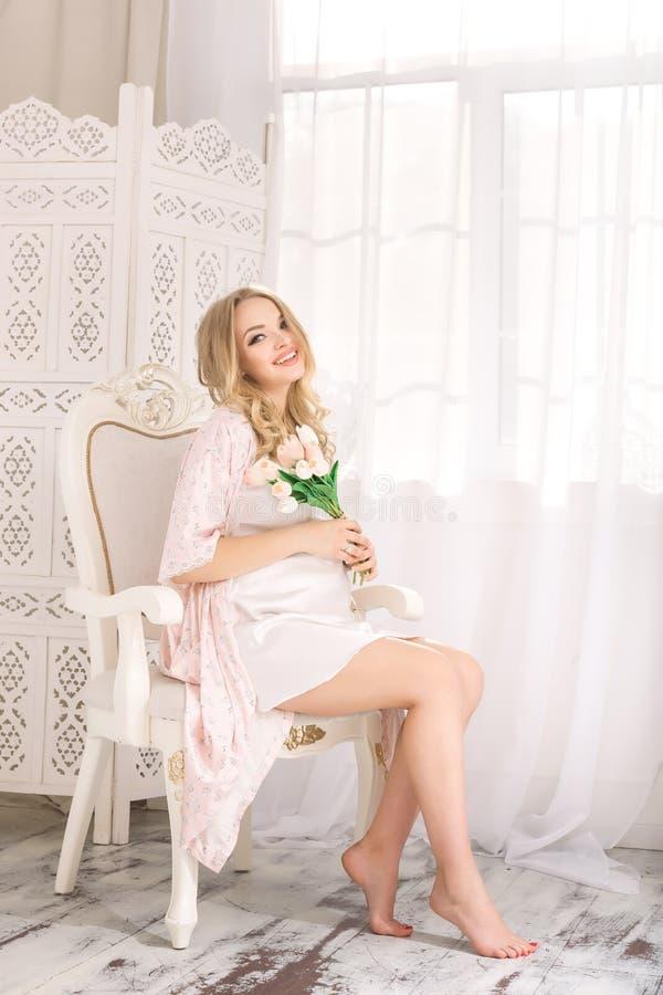 可爱的年轻白肤金发的孕妇坐在白色女睡袍的椅子 愉快的魅力性感的女孩在家 免版税库存图片