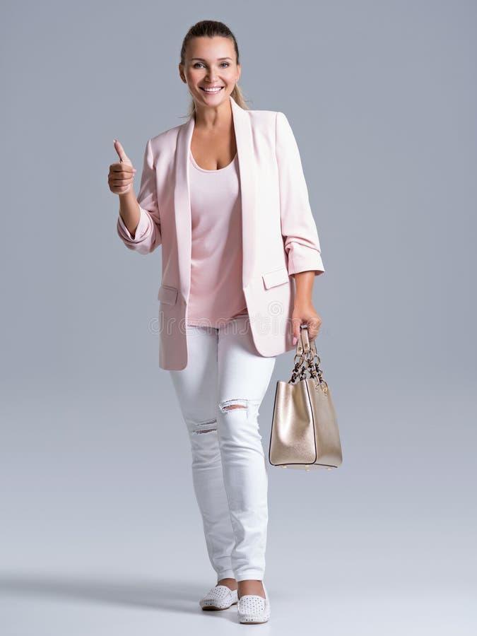 可爱的smilinge妇女拿着金黄提包 免版税库存照片