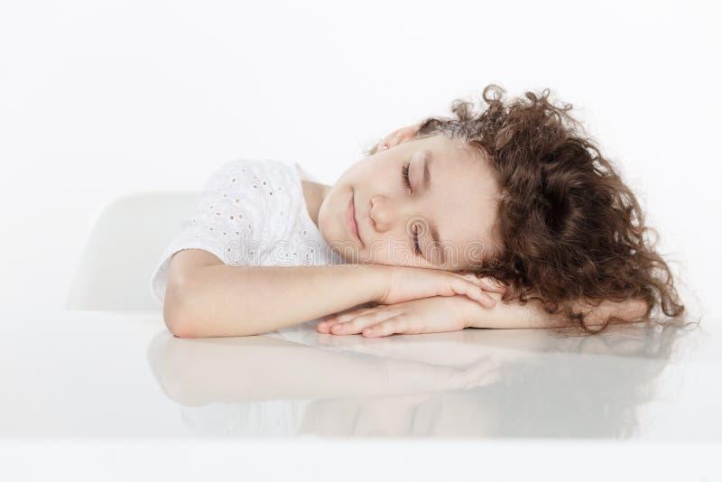 可爱矮小卷曲女孩睡觉paceful在一张桌上,在白色背景 E 库存照片