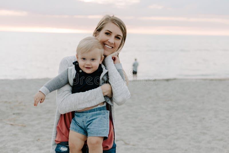 可爱笑,微笑和举行的完善的年轻母亲和小小孩儿子家庭在沙滩在太阳期间 免版税库存照片