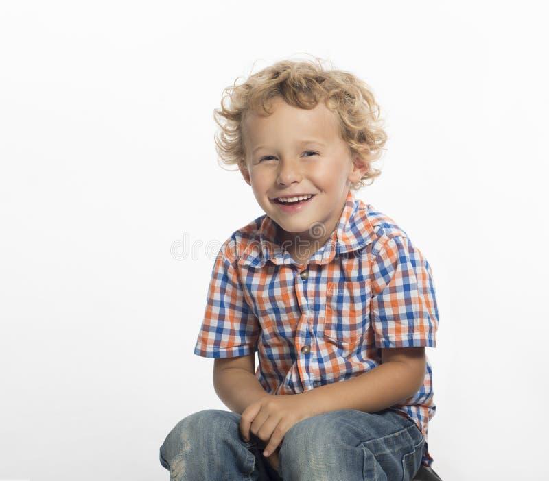 可爱,嘻嘻笑的小男孩,坐下 免版税库存照片