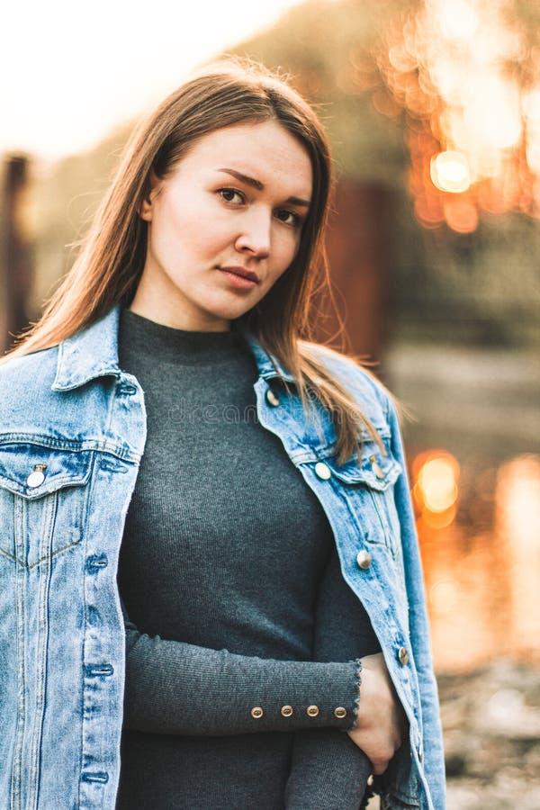 可爱,苗条,美丽的年轻白种人白肤金发的女孩的画象牛仔裤夹克的 微笑的女孩优良享用 免版税库存照片