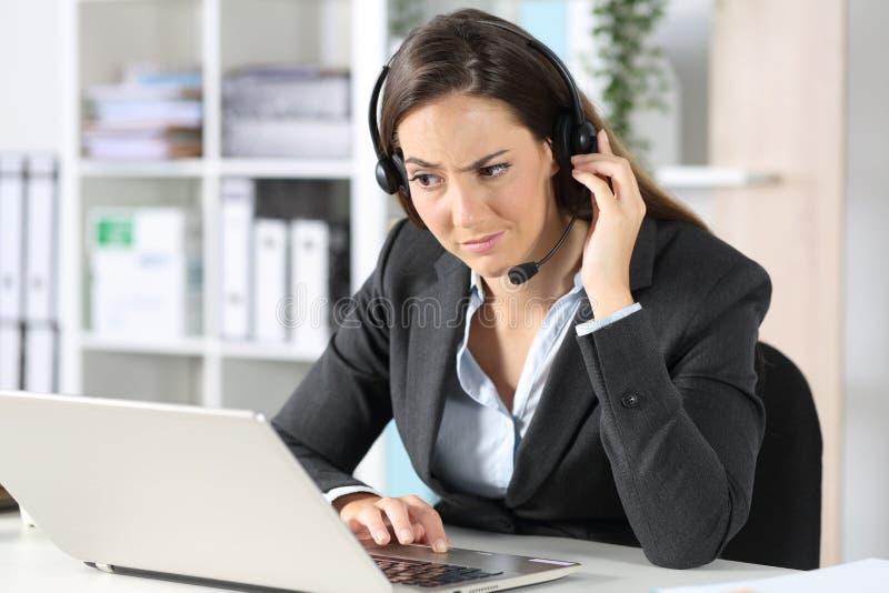 可疑电话营销员在办公室里看笔记本电脑 库存图片