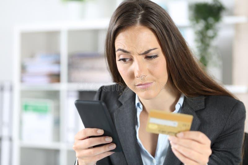 可疑的高管在办公室用电话付款 库存图片